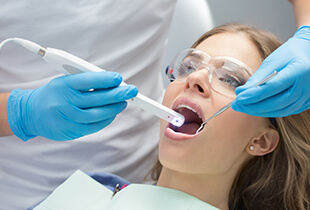 Dentist capturing intraoral photos of woman's smile