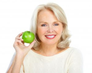woman smiling while holding apple