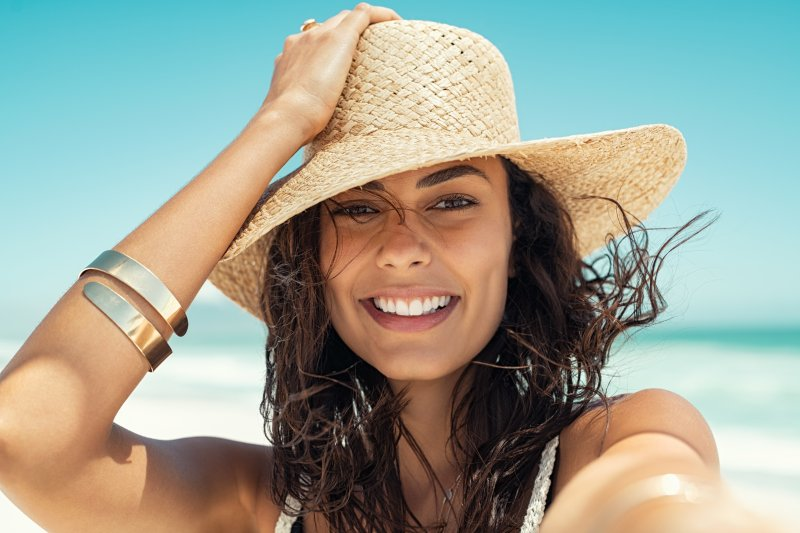 woman with straw hat smiling on beach during summer