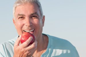 older man smiles holding apple